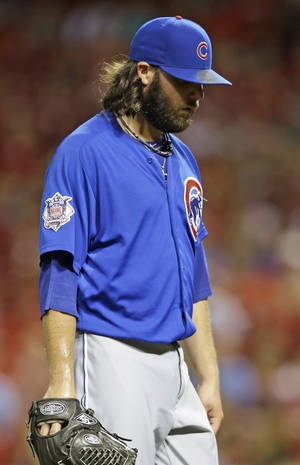 Photo - Chicago Cubs relief pitcher James Russell walks to the dugout at the end of the seventh inning of a baseball game against the Cincinnati Reds, Monday, July 7, 2014, in Cincinnati. Russell gave up a two-run home run to Jay Bruce in the inning. Cincinnati won 9-3. (AP Photo/Al Behrman)