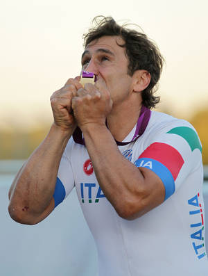 Photo -   Italy's Alessandro Zanardi celebrates winning the Gold Medal in the Men's Individual H 4 Road Race at Brands Hatch, Kent, during the Paralympic Games in London Friday September 7, 2012. (AP Photo/Gareth Fuller/PA) UNITED KINGDOM OUT NO SALES NO ARCHIVE