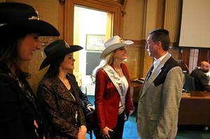 Photo - In this Jan. 22, 2014 photo, Colorado state representative Jerry Sonnenberg (R-Sterling) talks with Miss Rodeo America Paige Nicholson, inside the chambers of the Colorado State Legislature, at the Capitol, in Denver. Nicholson and fellow rodeo queens Codi Miller, center, and Ashley Fuchs were in town for the National Western Stock Show. Sonnenberg, a rancher who's the only farmer in the Colorado House, plans to push a radical idea this session: give each of his state's 64 counties one House seat apiece instead of electing representatives from districts with equal populations. ( AP Photo/Brennan Linsley)