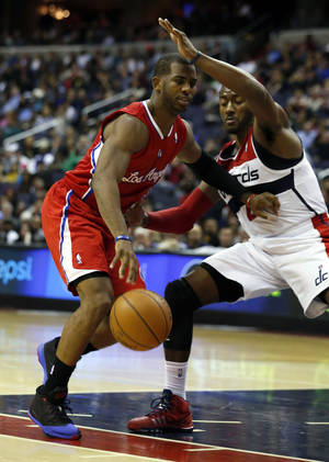 Photo - Los Angeles Clippers guard Chris Paul (3) drives against Washington Wizards guard John Wall (2) in the first half of an NBA basketball game, Saturday, Dec. 14, 2013, in Washington. (AP Photo/Alex Brandon)