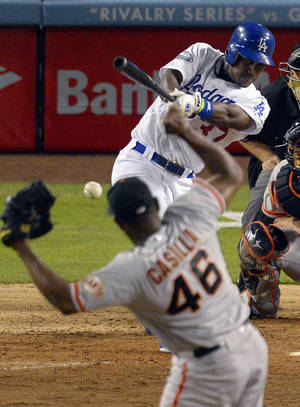 photo -   Los Angeles Dodgers' Elian Herrera, top, hits an RBI single to win the game as San Francisco Giants relief pitcher Santiago Casilla watches during the ninth inning of their baseball game, Monday, Oct. 1, 2012, in Los Angeles. (AP Photo/Mark J. Terrill)