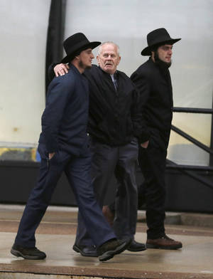 photo - Amish men walk to the U.S. Federal Courthouse Friday, Feb. 8, 2013, in Cleveland.  A judge will sentence 16 Amish for hate-crimes convictions in beard- and hair-cutting attacks on fellow Amish Friday, a case that highlighted issues of dissent and rogue discipline amid an idyllic rural lifestyle of horse buggies and wood stoves. (AP Photo/Tony Dejak)