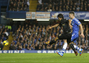 Photo - Manchester City's Sergio Aguero, left, scores a goal past Chelsea's Gary Cahill during the English Premier League soccer match between Chelsea and Manchester City at Stamford Bridge Stadium in London, Sunday, Oct. 27, 2013. (AP Photo/Kirsty Wigglesworth)