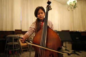 Photo - Gatewood Elementary School fourth-grader Izzabella (CQ)Truong-Richardson, 9,  plays the bass during a recent El Sistema Oklahoma practice.  <strong>SARAH PHIPPS - The Oklahoman</strong>