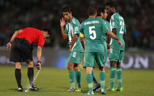 Photo - Referee Carlos Velasco of Spain marks a line with a spray during their semi final soccer match between Raja Casablanca and Atletico Mineiro at the Club World Cup soccer tournament in Marrakech, Morocco, Wednesday, Dec. 18, 2013. FIFA  referees use vanishing spray to mark out the distance for a defensive wall from a free kick. The spray is popular in South America but is not widely used elsewhere. Vanishing spray is unlikely to be used at the World Cup in Brazil. (AP Photo/Matthias Schrader)