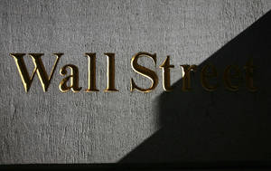 Photo - FILE - In this Monday, March 8, 2010, file photo, a sign for Wall Street is shown near the New York Stock Exchange. World stock markets struggled for direction Tuesday, June 24, 2014, after Wall Street fell for the first time in seven days, in a possible sign that investors were pausing to re-evaluate the market's recent highs. (AP Photo/Mark Lennihan, File)