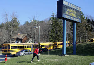 Photo - A woman walks onto the campus of the Franklin Regional School District where several people were stabbed at Franklin Regional High School on Wednesday, April 9, 2014, in Murrysville, Pa., near Pittsburgh. The suspect, a male student, was taken into custody and being questioned. (AP Photo/Gene J. Puskar)