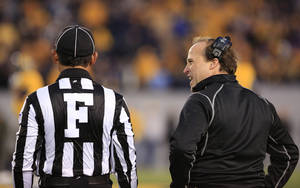 photo - West Virginia coach Dana Holgorsen, right, talks with an official during their NCAA college football game against TCU in Morgantown, W.Va., on Saturday, Nov. 3, 2012. (AP Photo/Christopher Jackson) ORG XMIT: WVCJ127