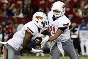 photo - Oklahoma State quarterback Wes Lunt (11) hands off to running back Joseph Randle, left, against Arizona during the first half of an NCAA college football game at Arizona Stadium in Tucson, Ariz., Saturday, Sept. 8, 2012. (AP Photo/Wily Low) ORG XMIT: AZWL102
