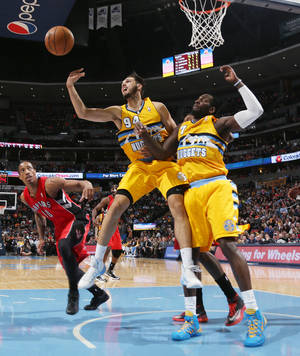 Photo - Denver Nuggets guard Evan Fournier, center, of France, reaches out for loose ball as forward J.J. Hickson, right, and Toronto Raptors guard DeMar DeRozan, left, cover in the third quarter of an NBA basketball game in Denver, Friday, Jan. 31, 2014. (AP Photo/David Zalubowski)
