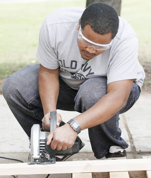 Photo - William Mwangi cuts a board in OU's WaTER Center field methods course Monday.