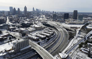 Photo - In this aerial view looking south toward downtown Atlanta, the ice-covered interstate system shows the remnants of a winter snow storm Wednesday, Jan. 29, 2014, in Atlanta. While such amounts of accumulation barely quality as a storm in the north, it was enough to paralyze the Deep South. (AP Photo/David Tulis)