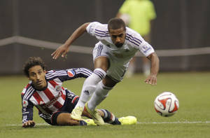 Photo - Swansea City's Wayne Routledge, right, chases down the ball against Chivas De Guadalajara's Fernando Arce, left, during the first half of a International League soccer match at Miller Park Wednesday, July 16, 2014, in Milwaukee. (AP Photo/Darren Hauck)