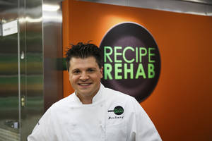 "Photo - In this Aug. 18, 2013 photo provided by Trium Entertainment, Lewisburg, W. Va., resident Rich Rosendale poses in front of a Recipe Rehab sign at the studios in Calabasas, Calif. Rosendale, one of TV's newest celebrity chefs, says his greatest challenges come on the set of ""Recipe Rehab,"" a Saturday morning show that begins airing Sept. 28 on CBS.  (AP Photo/Trium Entertainment, Venessa Stump)"