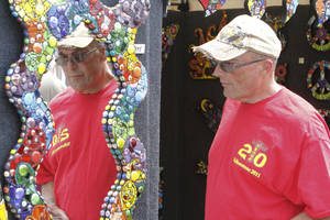 Photo - Tom Garrett looks at a colorful mirror during the Paseo Arts Festival in Oklahoma City, OK, Saturday, May 26, 2012,  By Paul Hellstern, The Oklahoman
