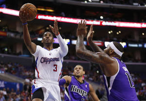 Photo - CORRECTS DAY OF WEEK TO SATURDAY - Los Angeles Clippers guard Chris Paul shoots the ball in front of Sacramento Kings guard Ray McCallum, center, and Kings center DeMarcus Cousins, right, during the first half of an NBA basketball game in Los Angeles, Saturday, April 12, 2014. (AP Photo/Danny Moloshok)