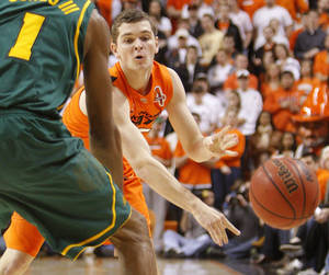 photo - OSU's Christien Sager (15) passes the ball in the first half of a men's college basketball game between the Oklahoma State University Cowboys and the Baylor University Bears at Gallagher-Iba Arena in Stillwater, Okla., Saturday, Feb. 4, 2012. Photo by Nate Billings, The Oklahoman