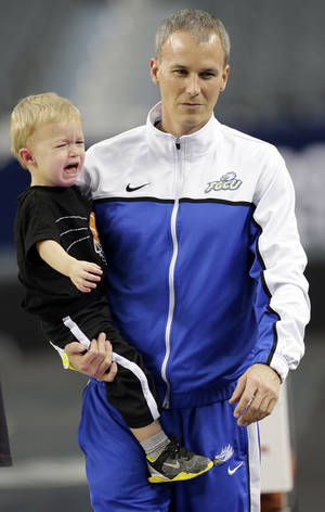 Photo - Florida Gulf Coast head coach Andy Enfield holds his son Marcum during practice for a regional semifinal game in the NCAA college basketball tournament, Thursday, March 28, 2013, in Arlington, Texas. Florida Gulf Coast faces Florida on Friday. (AP Photo/David J. Phillip) <strong>David J. Phillip</strong>