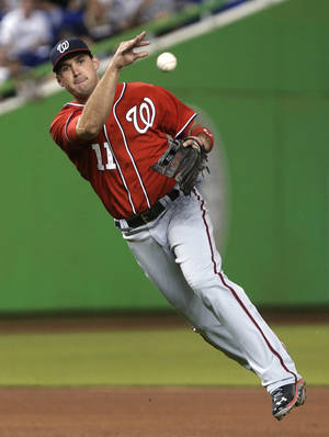 Photo - FILE - In this Sept. 7, 2013, file photo, Washington Nationals third baseman Ryan Zimmerman throws to first to put out a Miami Marlins batter during a baseball game in Miami. Zimmerman has a new piece of equipment in his locker--a first baseman's mitt. The Nationals' longtime third baseman will take some grounders on the opposite side of the diamond during spring training. Manager Matt Williams says he expects to use Zimmerman at first for a few games this season. (AP Photo/Wilfredo Lee, File)