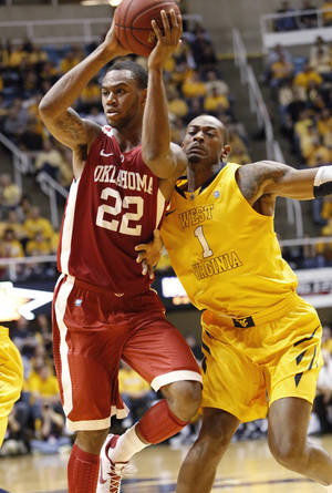photo - West Virginia's Dominique Rutledge, right, collides with Oklahoma's Amath M'Baye during an NCAA college basketball game in Morgantown, W.Va., Saturday, Jan. 5, 2013. Oklahoma won 67-57. (AP Photo/Randy Snyder)