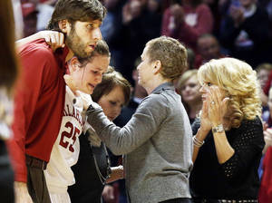 Photo - Whitney Hand, second from left, is helped off the court after an injury by strength coach Jozsef Szendrei, left, and trainer Carolyn Loon as she passes assistant coach Jan Ross, center, and head coach Sherri Coale during Thursday's game in Norman.  Photo by Steve Sisney, The Oklahoman