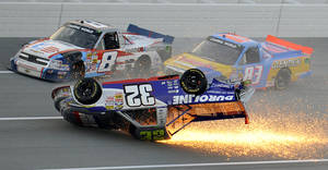 Photo - Max Gresham (8) and Chris Fontaine (83) get past a tumbling Miguel Paludo (32) on the final lap of the NASCAR Trucks auto race at Talladega Superspeedway in Talladega, Ala., Saturday, Oct. 19, 2013. (AP Photo/Dan Lighton)