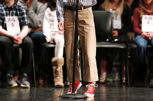 Photo - Above: A contestant stands on his toes to reach the microphone during a Scripps Regional Spelling Bee on Wednesday at John Marshall High School.