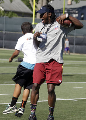 "photo -   Washington Redskins quarterback Robert Griffin III celebrates with a youngster during a youth camp as part of the NFL football rookie symposium at the Cleveland Browns training facility in Berea, Ohio Tuesday, June 26, 2012. A former Baylor basketball player is facing a federal extortion charge for allegedly threatening to release ""derogatory information"" about Heisman Trophy winner Robert Griffin III unless he was paid. (AP Photo/Mark Duncan)"