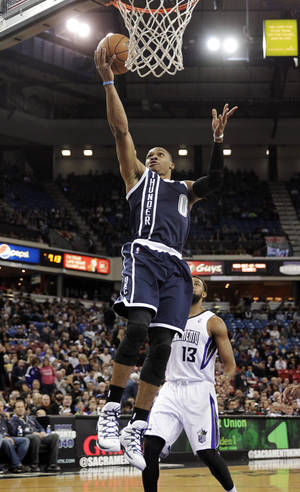 Photo - Oklahoma City Thunder guard Russell Westbrook, left, drives for the layup past Sacramento Kings forward Derrick Williams during the first quarter of an NBA basketball game in Sacramento, Calif., Tuesday, Dec. 3, 2013. (AP Photo/Rich Pedroncelli)