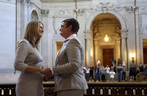 Photo - Sandy Stier, left, exchanges wedding vows with Kris Perry during a ceremony presided by California Attorney General Kamala Harris at City Hall in San Francisco, Friday,  June 28, 2013. Stier and Perry, the lead plaintiffs in the U.S. Supreme Court case that overturned California's same-sex marriage ban, tied the knot about an hour after a federal appeals court freed same-sex couples to obtain marriage licenses for the first time in 4 1/2 years. (AP Photo/Marcio Jose Sanchez)
