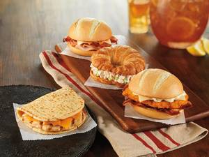 Photo - This product image provided by Dunkin' Donuts shows the chain's Grilled Chicken Flatbread, left, and bakery sandwich line. The chain has been expanding its sandwich offerings to bring in more business during the afternoon. But Dunkin' Brands CEO Nigel Travis said those sandwiches — which include fried chicken and grilled cheese varieties — shouldn't be considered lunch. (AP Photo/Dunkin' Donuts)