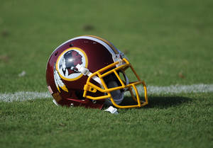 "Photo - A Washington Redskins football helmet lies on the field during NFL football minicamp, Wednesday, June 18, 2014, in Ashburn, Va. The U.S. Patent Office ruled Wednesday, June 18, 2014, that the Washington Redskins nickname is ""disparaging of Native Americans"" and that the team's federal trademarks for the name must be canceled. The ruling comes after a campaign to change the name has gained momentum over the past year.  (AP Photo/Nick Wass)"