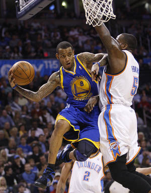 Photo - Golden State Warriors guard Monta Ellis, left, drives under the basket and passes in front of Oklahoma City Thunder center Kendrick Perkins during the first quarter of an NBA basketball game in Oklahoma City, Tuesday, March 29, 2011. (AP Photo/Sue Ogrocki) ORG XMIT: OKSO101