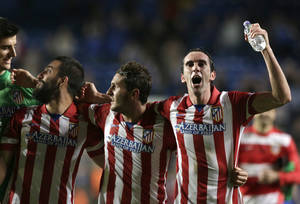Photo - Atletico goalkeeper Thibaut Courtois, left looks at Atletico's Arda Turan, second left as they celebrate after they defeated Chelsea in the Champions League semifinal second leg soccer match between Chelsea and Atletico Madrid at Stamford Bridge stadium in London, Wednesday, April 30, 2014. (AP Photo/Matt Dunham)