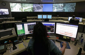 Photo - This Wednesday, April 24,2013 photo shows transportation engineer associate Abeer Kliefe working at the Los Angeles Department of Transportation's Automated Traffic Surveillance and Control Center in downtown Los Angeles. In small towns and big cities, police and politicians are pointing to the surveillance video that was key to identifying the Boston Marathon bombing suspects as a reason to bolster their own networks and get more electronic eyes on their streets. In Los Angeles, a councilman wants police to broaden their network by giving them access to traffic cameras used to monitor the flow of cars on the road. (AP Photo/Reed Saxon)