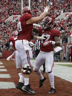 Photo - Alabama running back Kenyan Drake (17) celebrates with offensive linesman Ryan Kelly (70) after scoring on a 13-yard touchdown run against Chattanooga during the first half of an NCAA college football game in Tuscaloosa, Ala., Saturday, Nov. 23, 2013. (AP Photo/Dave Martin)