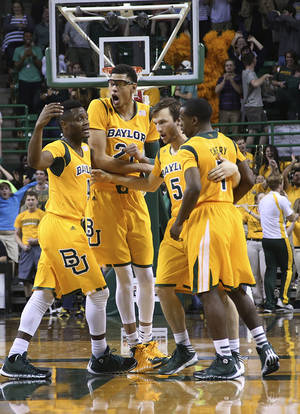 Photo - Baylor guard Brady Heslip (5) huddles with teammatesIsaiah Austin (21), Gary Franklin, left, and Kenny Chery, right, after scoring on a 3-point play in the second half of an NCAA college basketball game, Saturday, Feb. 15, 2014, in Waco, Texas. (AP Photo/Waco Tribune Herald, Rod Aydelotte)