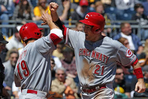 Photo - Cincinnati Reds' Todd Frazier (21) celebrates with Joey Votto (19) after they scored on a double by Reds' Ryan Ludwick off Pittsburgh Pirates starting pitcher Brandon Cumpton during the sixth inning of a baseball game in Pittsburgh Thursday, April 24, 2014. (AP Photo/Gene J. Puskar)