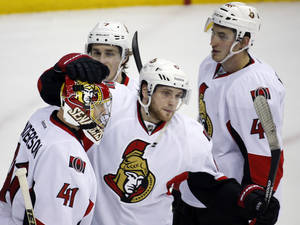 Photo - Ottawa Senators goalie Craig Anderson (41) celebrates with teammates center Kyle Turris (7), right wing Bobby Ryan (6) and defenseman Patrick Wiercioch (46) after an NHL hockey game against the Washington Capitals, Tuesday, Jan. 21, 2014, in Washington. The Senators won 2-0. (AP Photo/Alex Brandon)