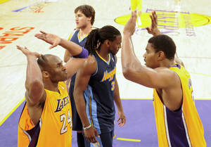 Photo -   Los Angeles Lakers' Kobe Bryant, left, celebrates with Andrew Bynum, as Denver Nuggets' Kenneth Faried, middle, looks away during the second half of a NBA first-round playoff basketball game in Los Angeles, Tuesday, May 1, 2012. The Lakers won 104-100. (AP Photo/Chris Carlson)
