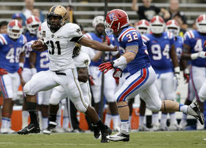 Photo - Army running back Terry Baggett (31) holds off Louisiana Tech linebacker Mitch Villemez (32) as Baggett gains extra yardage on a long run in the first half of a NCAA college football game, Saturday, Sept. 28, 2013, in Dallas. (AP Photo/Tony Gutierrez)