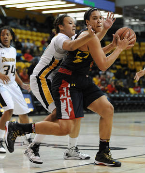 Photo - Maryland's Brionna Jones, right, looks to shoot as Towson's Camille Alberson, left, defends in the second half of an NCAA college basketball game on Saturday, Nov. 23, 2013, in Towson, Md. Maryland won 90-53. (AP Photo/Gail Burton)