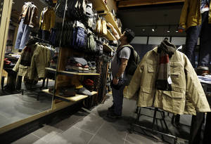 Photo - In this Friday, Oct. 4, 2013, photo, a shopper browses at a Timberland store in Skokie, Ill. The Conference Board releases the Consumer Confidence Index for October on Tuesday, Oct. 29, 2013. (AP Photo/Nam Y. Huh)