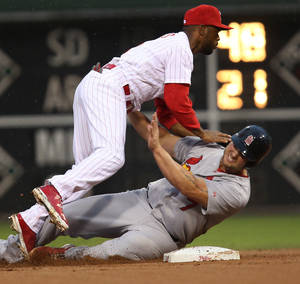 Photo - St Louis Cardinals' Matt Holliday, bottom, is out at second and Philadelphia Phillies' Jimmy Rollins throws to first on a ground ball hit by Cardinals' Matt Adams in the first inning of a baseball game, Saturday, Aug. 23, 2014, in Philadelphia. (AP Photo/Laurence Kesterson)