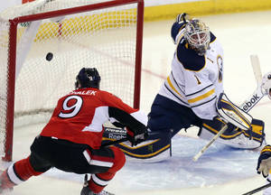Photo - Ottawa Senators' Milan Michalek (9) scores on Buffalo Sabres goaltender Jhonas Enroth (1) during the third period of an NHL hockey game, Thursday, Feb. 6, 2014 in Ottawa, Ontario. Ottawa defeated Buffalo 3-2. (AP Photo/The Canadian Press, Fred Chartrand)