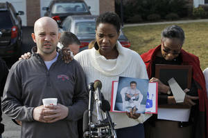 Photo - Shawn Gordley, left, and Jennea Gordley, center, parents of Caleb Gordley, accompanied by family and friends of Caleb Gordley, talk to members of the media outside their home in Sterling, Va., Tuesday, March 19, 2013. Police say Caleb Gordley, a Loudoun County teenager was shot and killed after he climbed into a neighbor's home through a back window.  (AP Photo/Ann Heisenfelt)