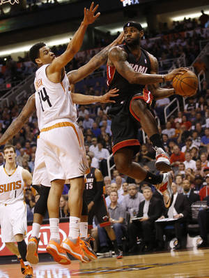 Photo - Miami Heat forward LeBron James passes the ball off while defended by Phoenix Suns guard Gerald Green during the first half of an NBA basketball game Tuesday, Feb. 11, 2014, in Phoenix. (AP Photo/The Arizona Republic, Michael Chow) MAGS OUT  NO SALES  MESA OUT  MARICOPA COUNTY OUT