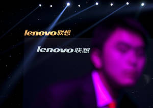 Photo - FILE - In this Aug. 6, 2012 file photo, a Lenovo employee, front, walks near the company logos during a Lenovo promotional event in Beijing, China. Lenovo said Thursday Jan. 23, 2014  it is acquiring IBM's x86 server business and expects to offer jobs to 7,500 IBM employees in locations around the world. (AP Photo/Alexander F. Yuan, File)