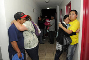 Photo - People embrace on the upper floor of an apartment building located a few blocks from the coast where they gathered to avoid a possible tsunami after an earthquake in Iquique, Chile, Tuesday, April 1, 2014. A powerful magnitude-8.2 earthquake struck off Chile's northern coast Tuesday night. There were no immediate reports of injuries or major damage, but buildings shook in nearby Peru and in Bolivia's high altitude capital of La Paz. (AP Photo/Cristian Viveros) NO PUBLICAR EN CHILE