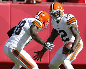 Photo - Cleveland Browns wide receiver Josh Gordon (12) celebrates his touchdown with teammate Greg Little (18) during the first half of an NFL football game against the Kansas City Chiefs in Kansas City, Mo., Sunday, Oct. 27, 2013. (AP Photo/Colin E. Braley)
